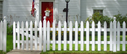 Image of a picket fence in front of a house