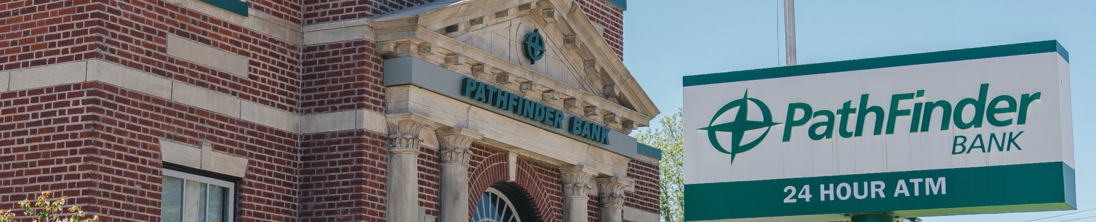 Pathfinder Bank Lacona branch with a branded 24 Hour ATM sign in the front yard.