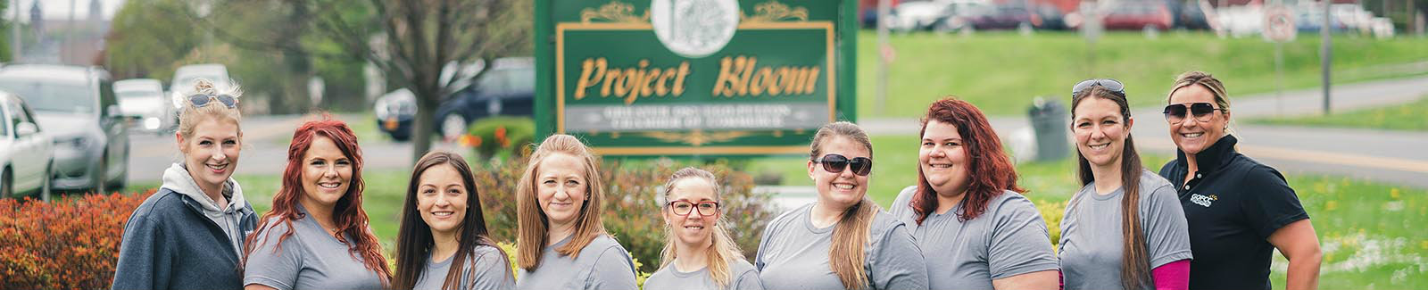 A group of Pathfinder employees together at a volunteer event for Project Bloom, smiling for a picture.