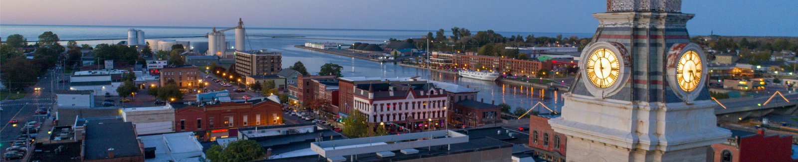 Aerial view of Oswego City Hall at sunset in the foreground, with the view of the Oswego River, harbor/pier, and horizon in the background.
