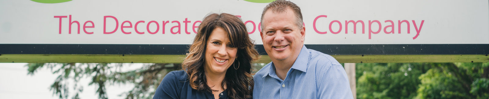 Pete Hess and Tina Corso-Hess, Corso's Cookies owners in front of their business sign.