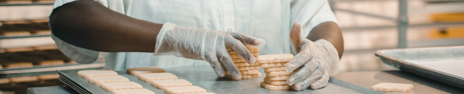 Baker stacking freshly baked sugar cookies on a tray