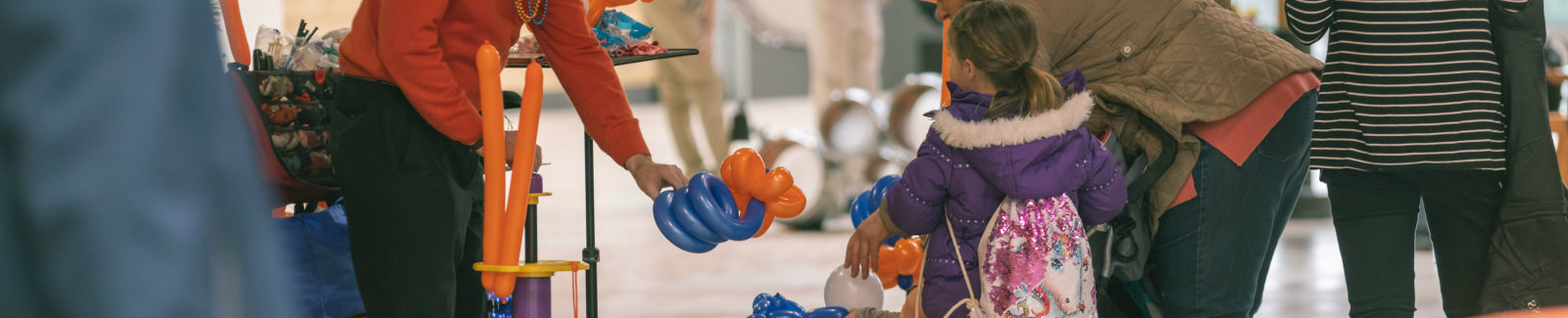 Little girl getting a balloon animal from a friendly clown in Destiny USA mall.