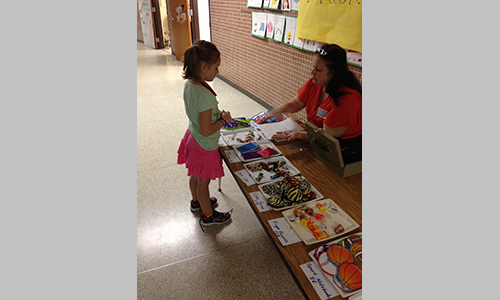 Coon Rapids staff member, Debby Gmitter, helping Madison Sombrio at the school store